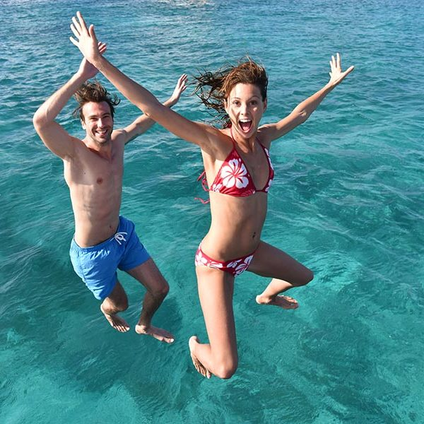 Couple jumping from boat at birthday boat rental in Honolulu